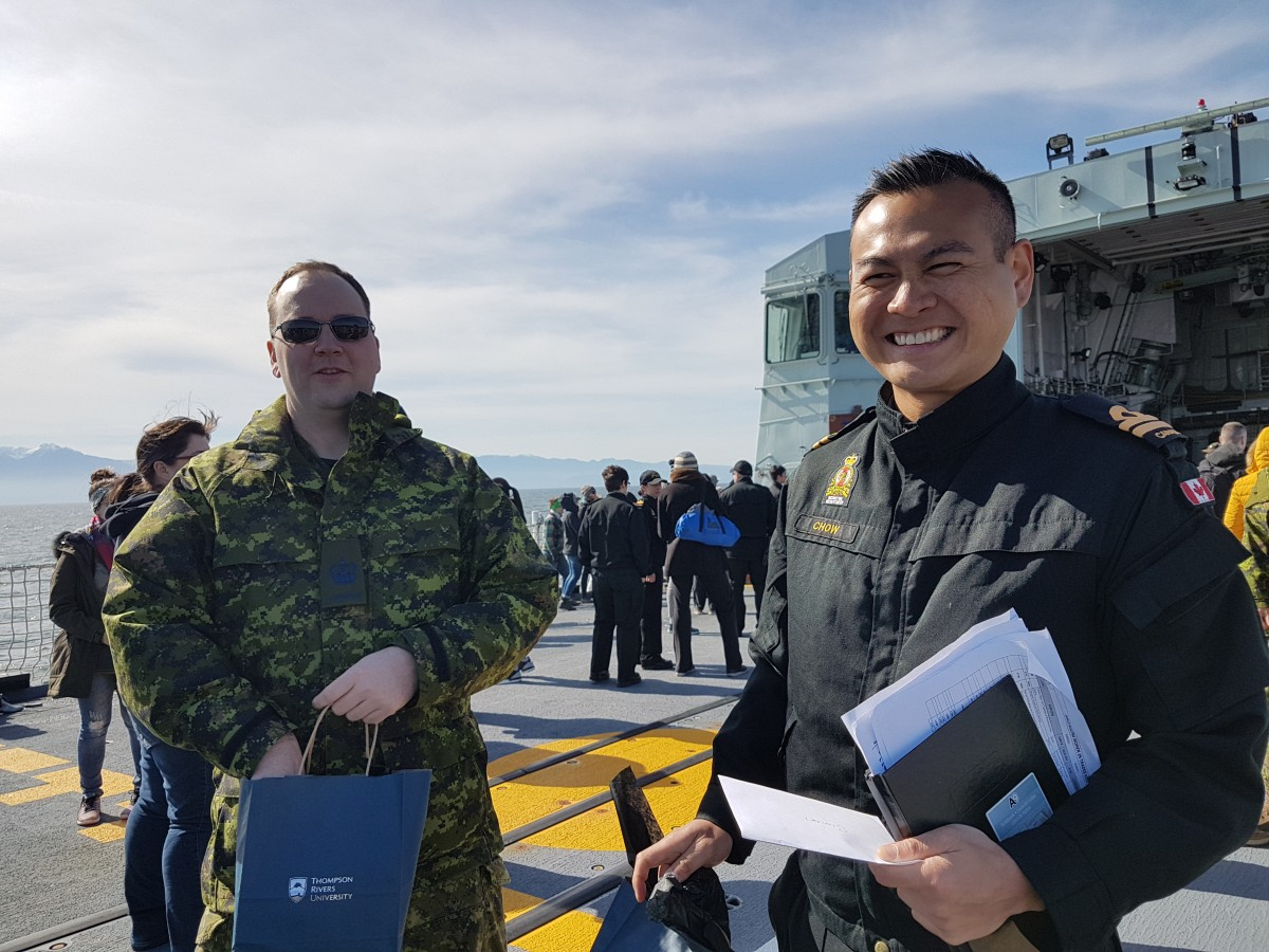 Warrant Officer Jeffrey Bateman and Lt. Simon Chow accepting TRU gifts as a thank you for the invitation on the HMCS Regina